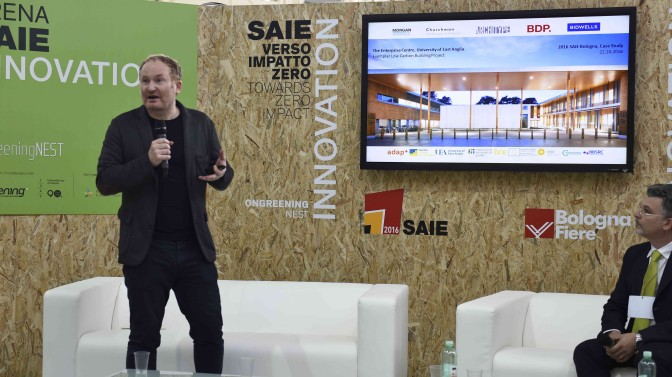 Architect James Todd speaking on stage in Bologna