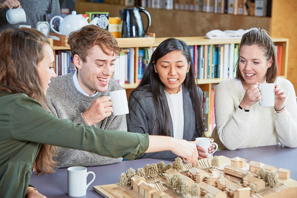 4 architectural assistants discuss building model