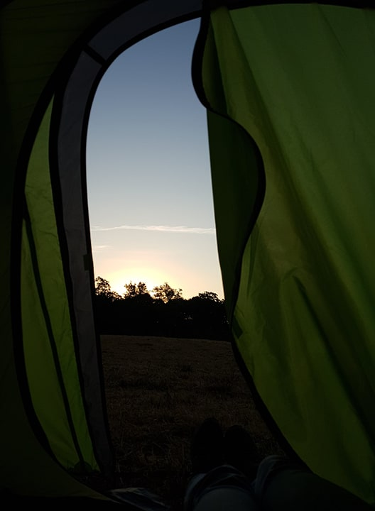 View of the sunrise from open tent door