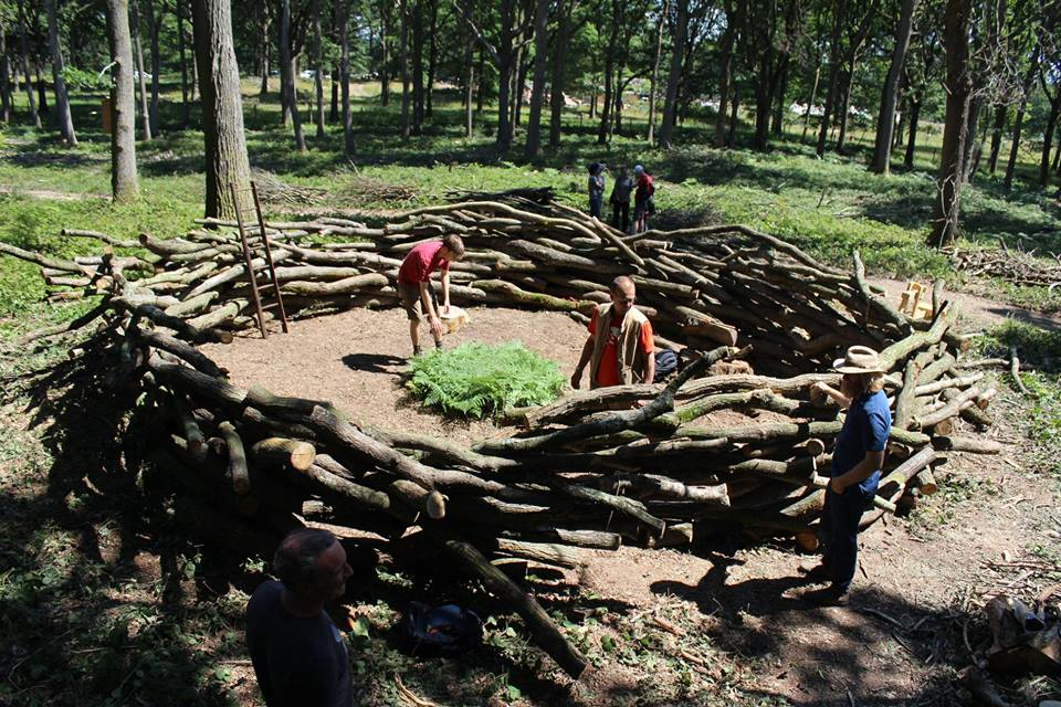 Students building the round timber structure