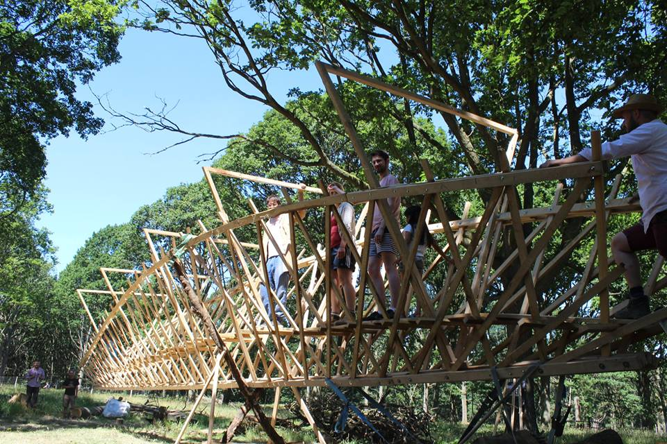 Photo of students walking on truss structure made of sections of oak