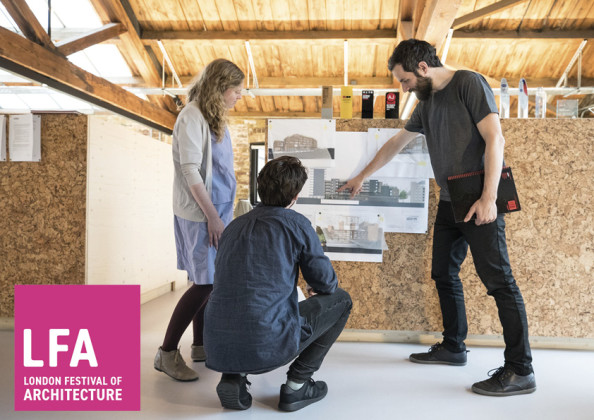 Three members of the Architype team stand in the light and airy London office. Surrounded by natural timber, they point at a housing scheme render attached to a cork board. The logo in the corner reads 'LFA London Festival of Architecture.'
